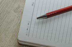 Notebook and pen in composition in red and white Stock Photography