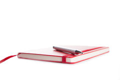 Notebook and pen in composition in red and white Royalty Free Stock Images