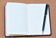 Notebook with pen on cork background Royalty Free Stock Photography
