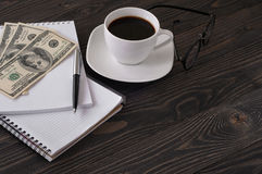 Notebook with pen, cup of coffee, dollars and glasses Stock Photos