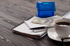 Notebook with a pen, cup of coffee, money and house Royalty Free Stock Photography