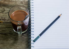 Notebook pen and cup of coffee in wood table Royalty Free Stock Images