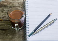 Notebook pen and cup of coffee in wood table Royalty Free Stock Photography
