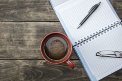 Notebook pen and cup of coffee on wood table Royalty Free Stock Images