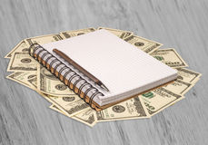 Notebook pen Dolar money on a wooden table Royalty Free Stock Images