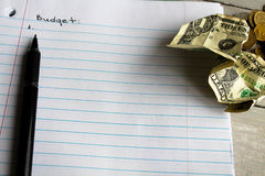 Notebook pen dollar coins budget planning Stock Image
