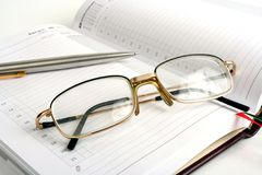 Notebook, pen and eyeglasses Royalty Free Stock Image