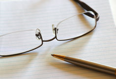 Notebook, Pen and Eyeglasses. Open Notebook, Pen and Eyeglasses. Shallow Depth of Field stock photo