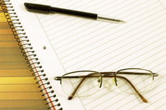 Notebook pen and eyeglasses Stock Images