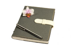 Notebook with pen and flower and orchid. The notebook it kept all the plan and the memory Royalty Free Stock Photo