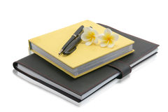 Notebook with pen and flower on a white background Royalty Free Stock Image