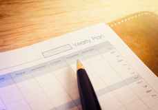 Notebook and pen focus on yearly plan wording message Royalty Free Stock Photography