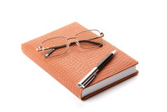 Notebook, pen and glasses Stock Image