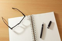 Notebook with pen and glasses Stock Photography