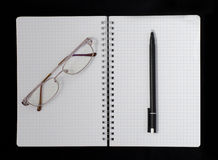 Notebook, pen and glasses. On a dark background Stock Photography