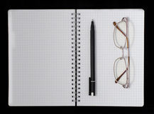 Notebook, pen and glasses. On a dark background Stock Image