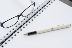 Notebook pen and glasses. Stock Photo