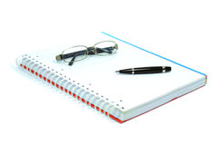 Notebook, pen and glasses Stock Photo