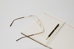 Notebook  pen and glasses Stock Images