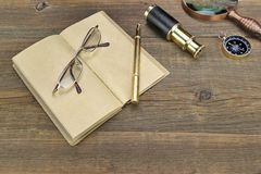 Notebook, Pen, Glasses, Magnifier, Cpmpass and Spyglass On Wood Stock Photo