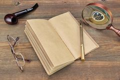 Notebook, Pen, Glasses, Magnifier and Smoking Pipe On Wood Backg Stock Image