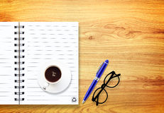 Notebook with pen and glasses  on wood Stock Photo