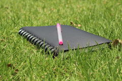 Notebook and  pen on grass Royalty Free Stock Images