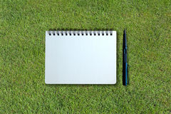 Notebook and pen on grass texture Stock Images