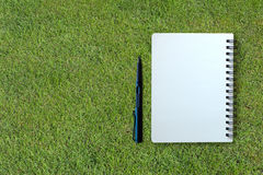 Notebook and pen on grass texture Stock Photography