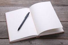 Notebook and pen on grey wood background royalty free stock photos