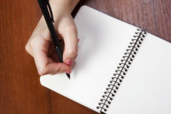 Notebook and pen in hand.  on white background. Royalty Free Stock Images