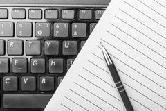 Notebook and pen on the keyboard. Notebook and pen on the black keyboard stock image
