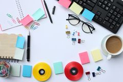 Notebook,pen,keyboard, coffee mug and accessories placed on a wh stock photography