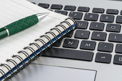 Notebook and pen on the laptop keyboard, close up Royalty Free Stock Photography