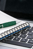 Notebook and pen on the laptop keyboard, close up Stock Photo