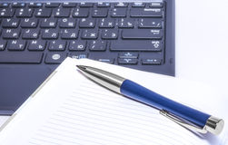 Notebook and pen lie on the keyboard of computer Stock Photos