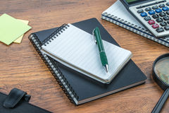 Notebook, pen and Magnifier with Calculator on the desk Royalty Free Stock Photo