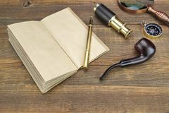 Notebook, Pen, Magnifier, Cpmpass, Pipe, Spyglass On Wood Backgr Royalty Free Stock Photos