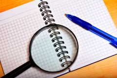 Notebook, pen and magnifier Stock Photos