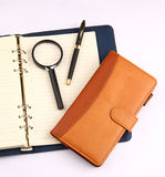 Notebook pen and magnifying glass. On white background Royalty Free Stock Photography