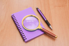 Notebook pen and magnifying glass Stock Photography
