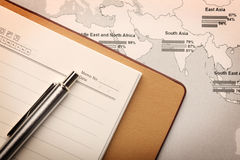 Notebook and pen on a map Stock Photography