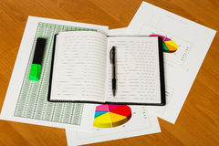 Notebook, pen, marker and sheets with graphics on  desktop. Stock Images