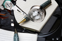 Notebook and pen mirrored in hard disk platter Royalty Free Stock Photography