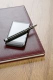 Notebook with pen and mobile phone Royalty Free Stock Photos