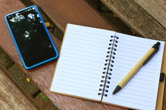 Notebook with pen and mobile phone on the brown bench Stock Image