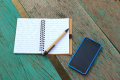 Notebook with pen and mobile phone on the green table Royalty Free Stock Photo