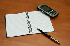 Notebook pen and mobile phone on table Royalty Free Stock Photo