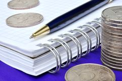 Notebook, pen and money. Blue pen, notebook and russian coins Royalty Free Stock Image