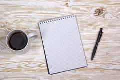 Notebook with pen and mug  on wooden table Royalty Free Stock Photography